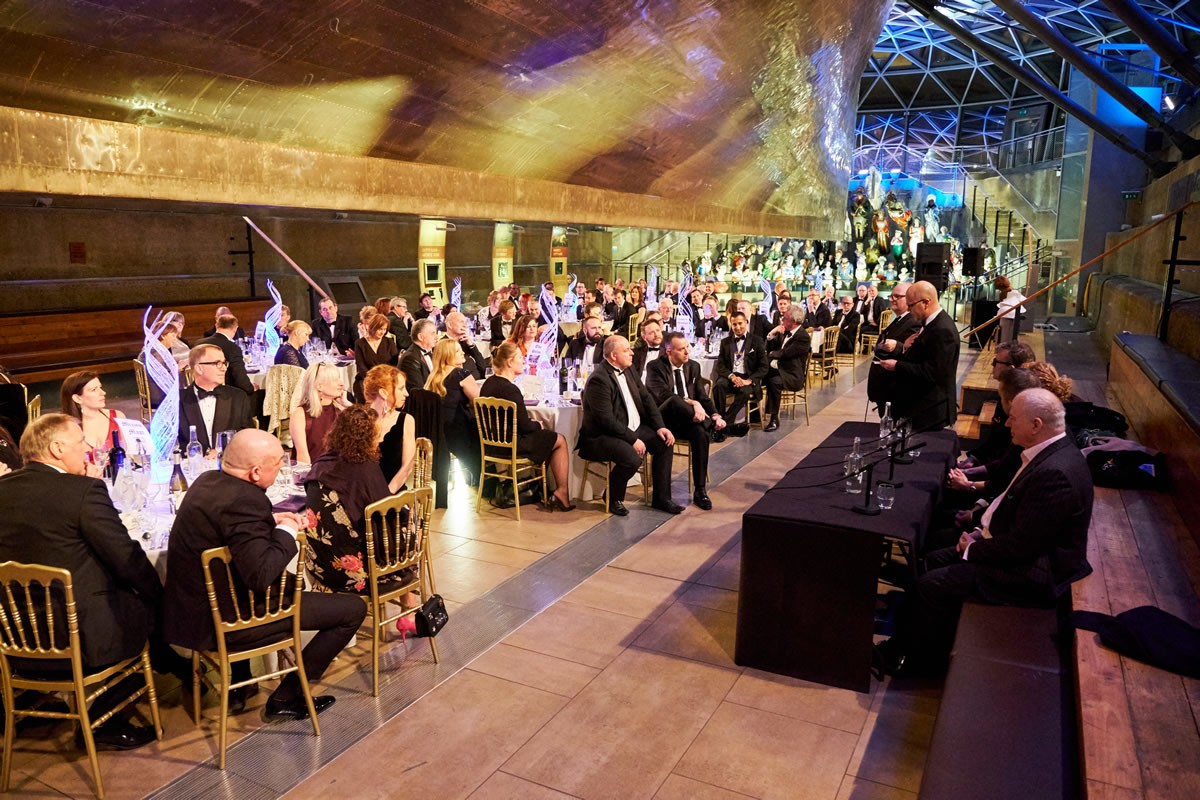 a wide shot of the guests under the hull of the Cutty Sark listening to a panel of speakers