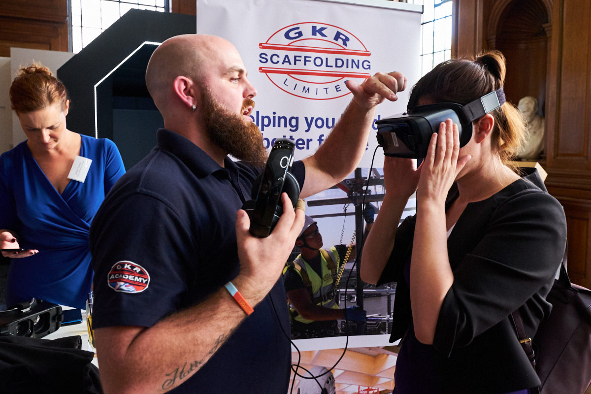 a technician fitting some virtual reality goggles on a guest