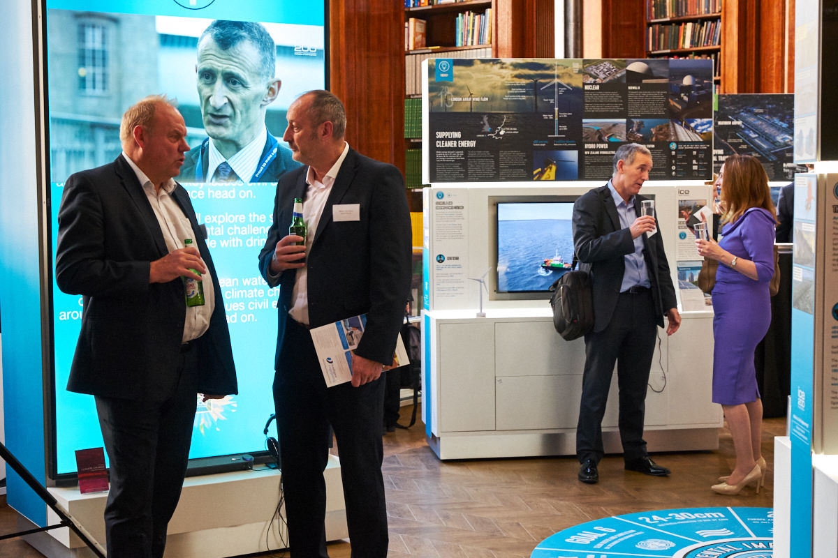 guests at a London event standing in front of a screen