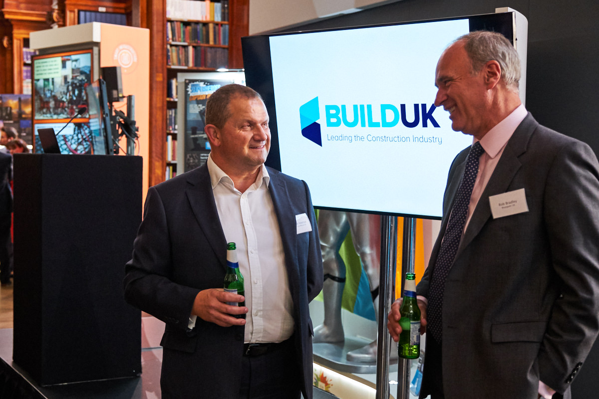 guests talking in front of a Build UK branded screen