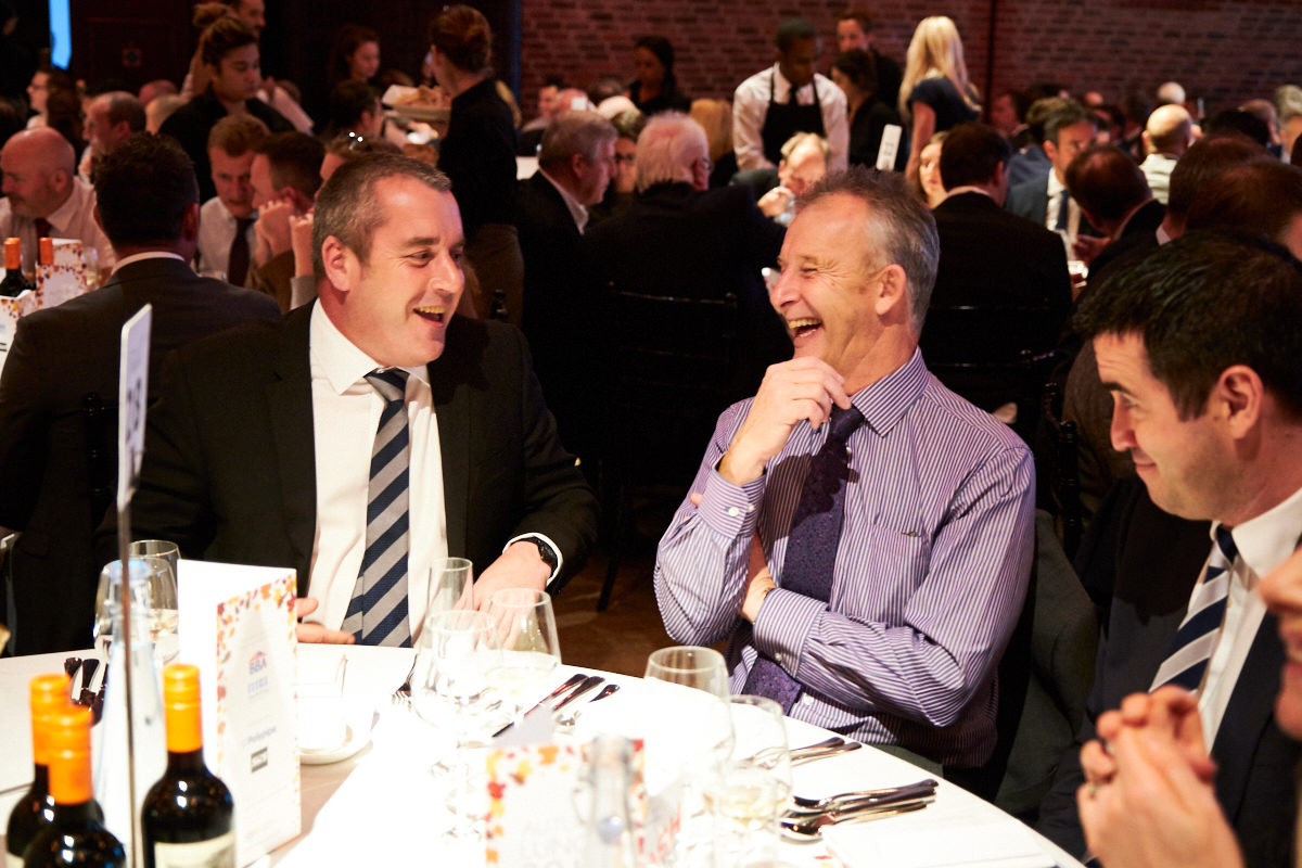 two guests at an event laughing