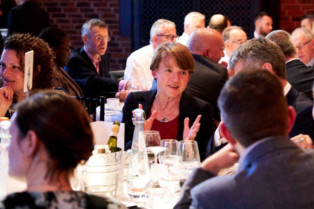 a guest talking across a table to another guest at a London event