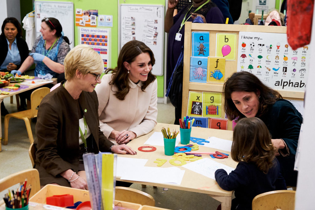 The Duchess of Cambridge talking to children while being photographed by a professional photographer