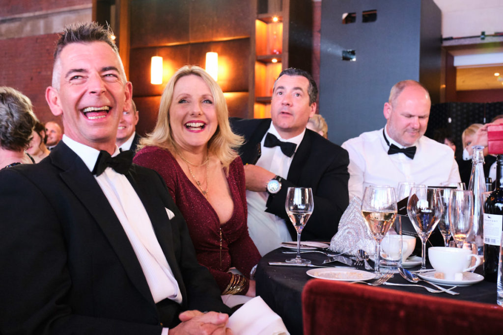guests laughing at an event in London