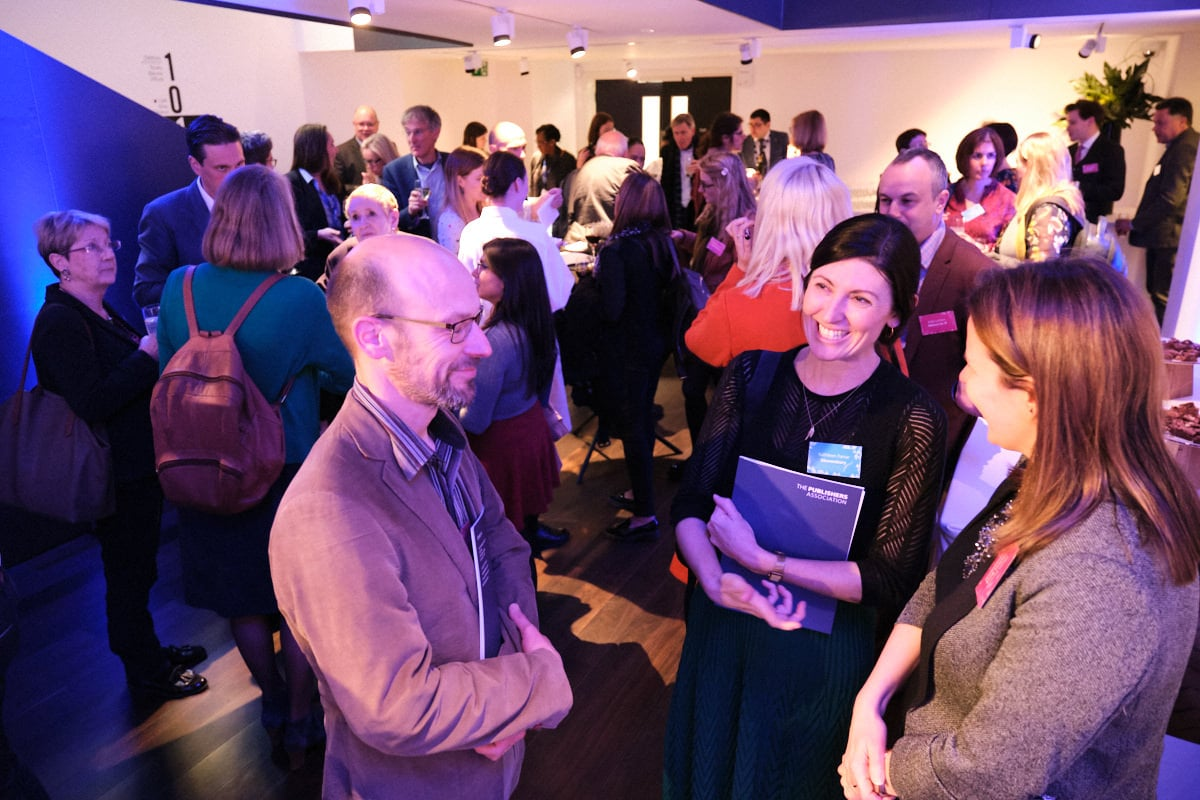 delegates at a London event talking and laughing