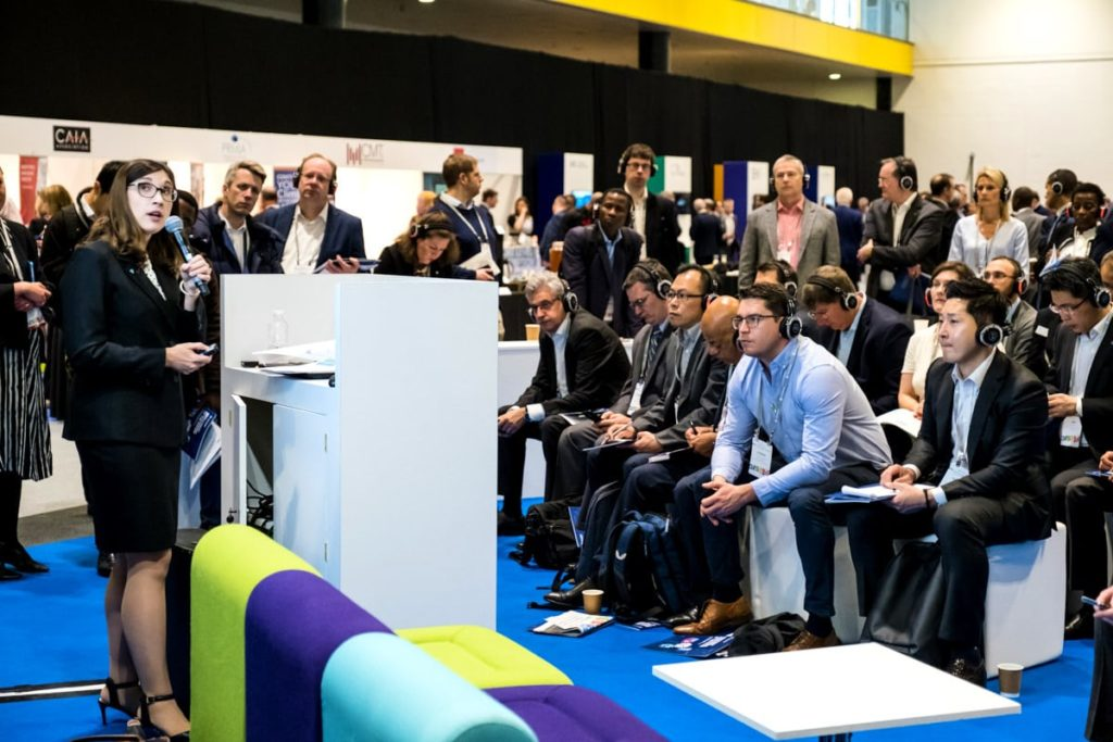 Delegates listening to a speaker at a conference at the ExCeL London