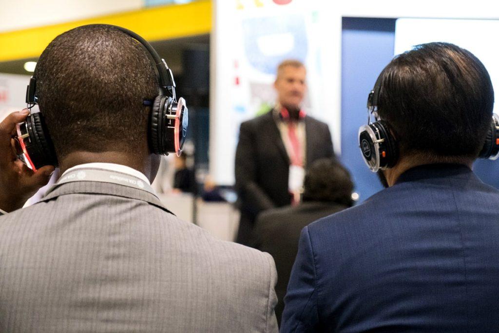 Delegates listening to a speaker through headphones