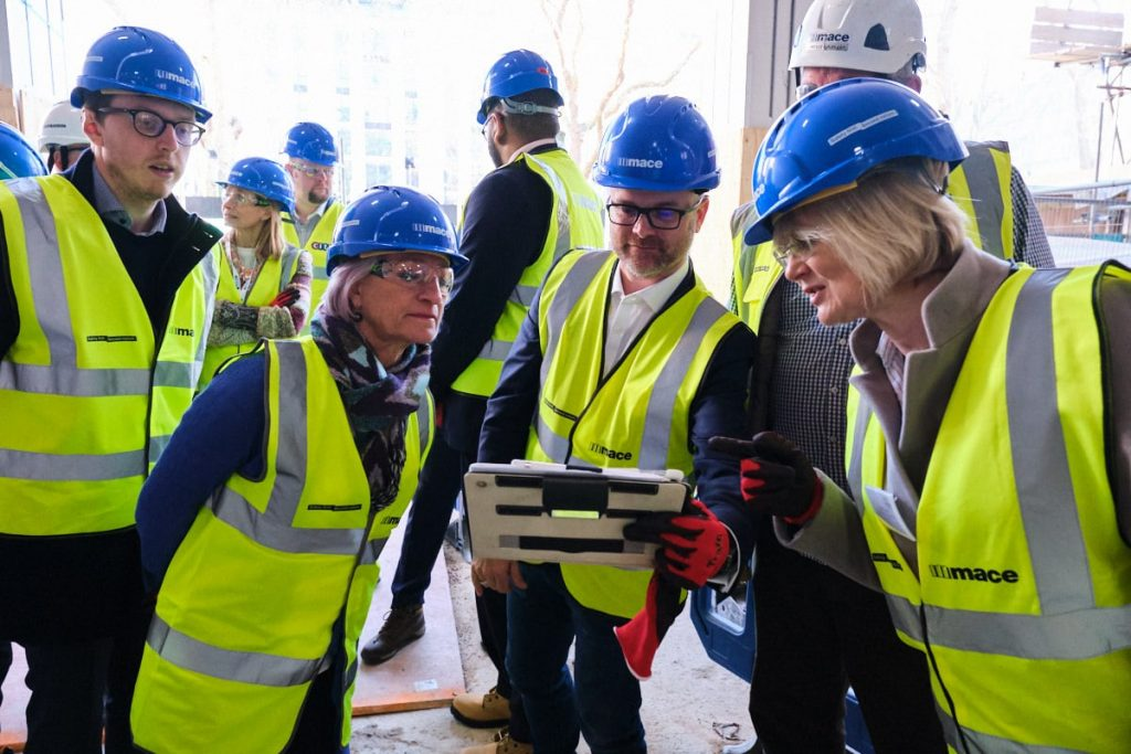 Visitors to a building site in London looking at an iPad