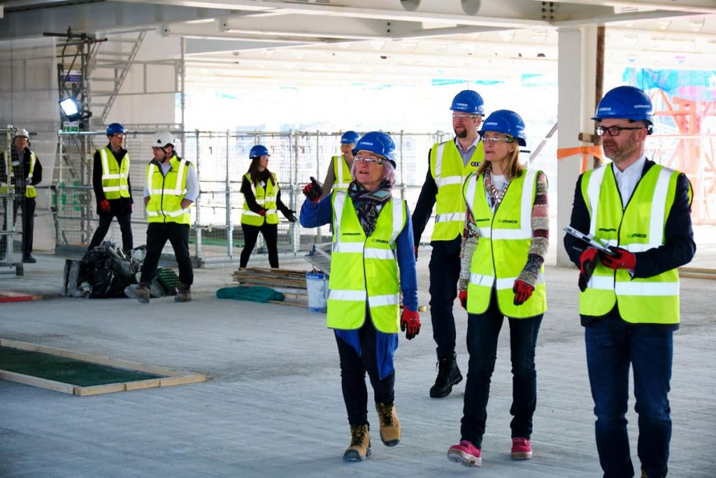 Visitors to a building site talk about what they are seeing